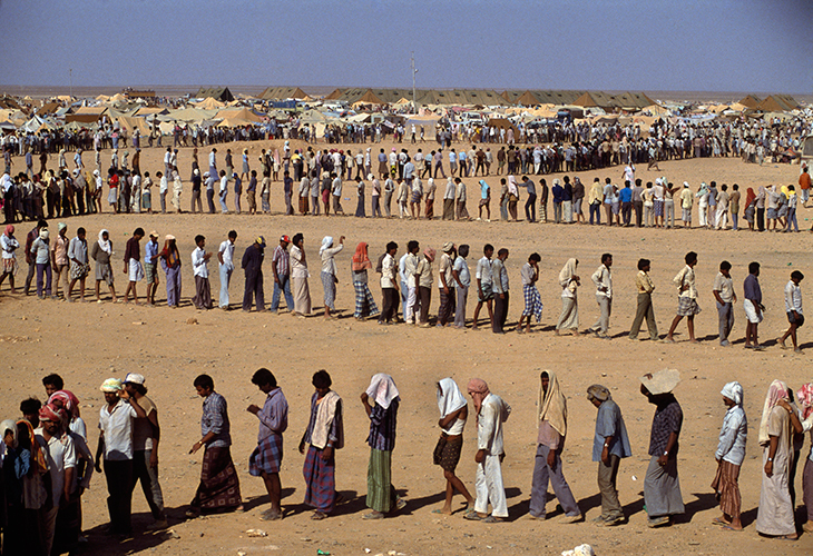 """Refugees in the desert. The Sha-alaan One camp, is the worst camp. They have orderly food lines with thousands of refugees waiting calmly for food distribution from the """"Charitas"""" charity organization. Jordan, 1990. © Chris Steele-Perkins / Magnum Photos"""